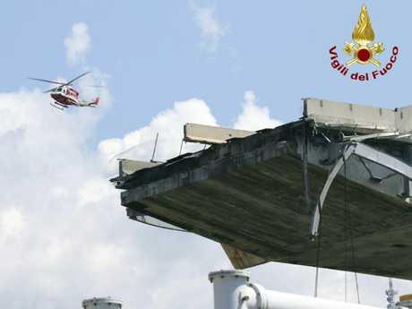 A firefighter helicopter hovers over the collapsed Morandi Bridge. Picture: Vigili del Fuoco via AP