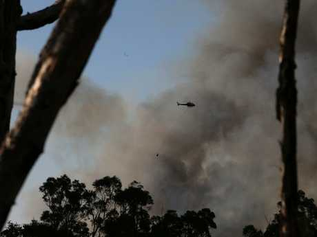 A water bombing helicopter fights the fires from the sky. Picture: Peter Lorimer