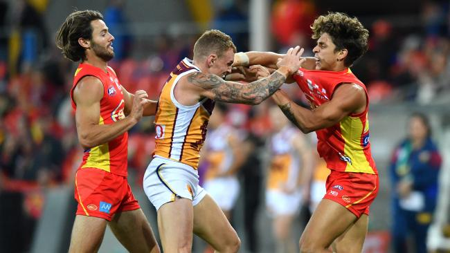 Mitch Robinson (centre) of the Lions wrestles with Lachie Weller (left) and Sean Lemmens (right). Pic: AAP