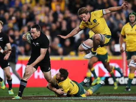 New Zealand's Ben Smith attacks as Australia's Michael Hooper flies high while giving chase. Picture: Brett Costello
