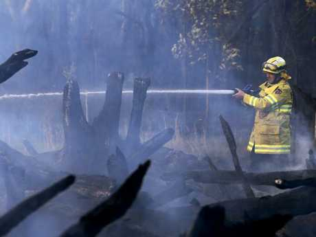 A firefighter extinguishes a fire in Salt Ash today. Picture: AAP