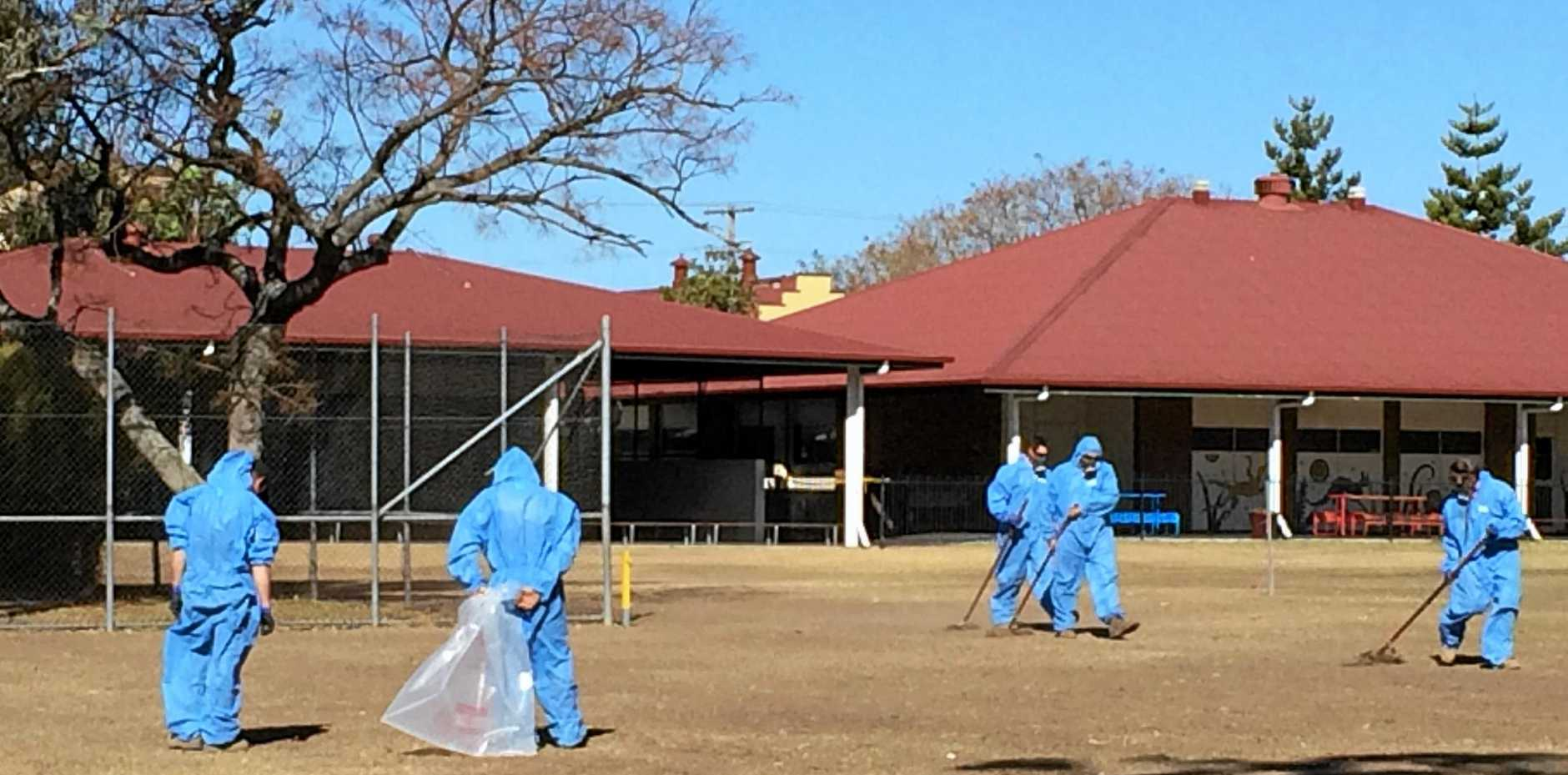 Asbestos consultants contracted by Workplace Health and Safety Queensland perform soil tests on the oval and playground area at Warwick Central State School on Saturday.