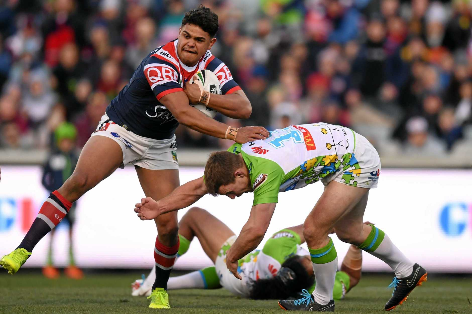 Latrell Mitchell leaves a string of Raiders defenders in his wake.
