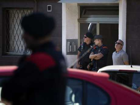 Catalan police officers stand guard at the entrance of a building during a raid following an attack in Cornella de Llobregat near Barcelona.