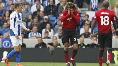 Manchester United's Marouane Fellaini has his head in his hands.