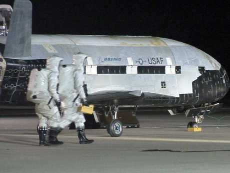 An X-37B is approached by ground personnel after spending more than a year in orbit. What the reusable space-plane does up there is anybody's guess.