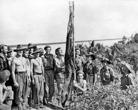 Australian soldiers flying the flag on the shores of Tarakan Island in May 1945.