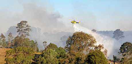 Helicopters water bomb a fire at North Deep Creek on Monday.