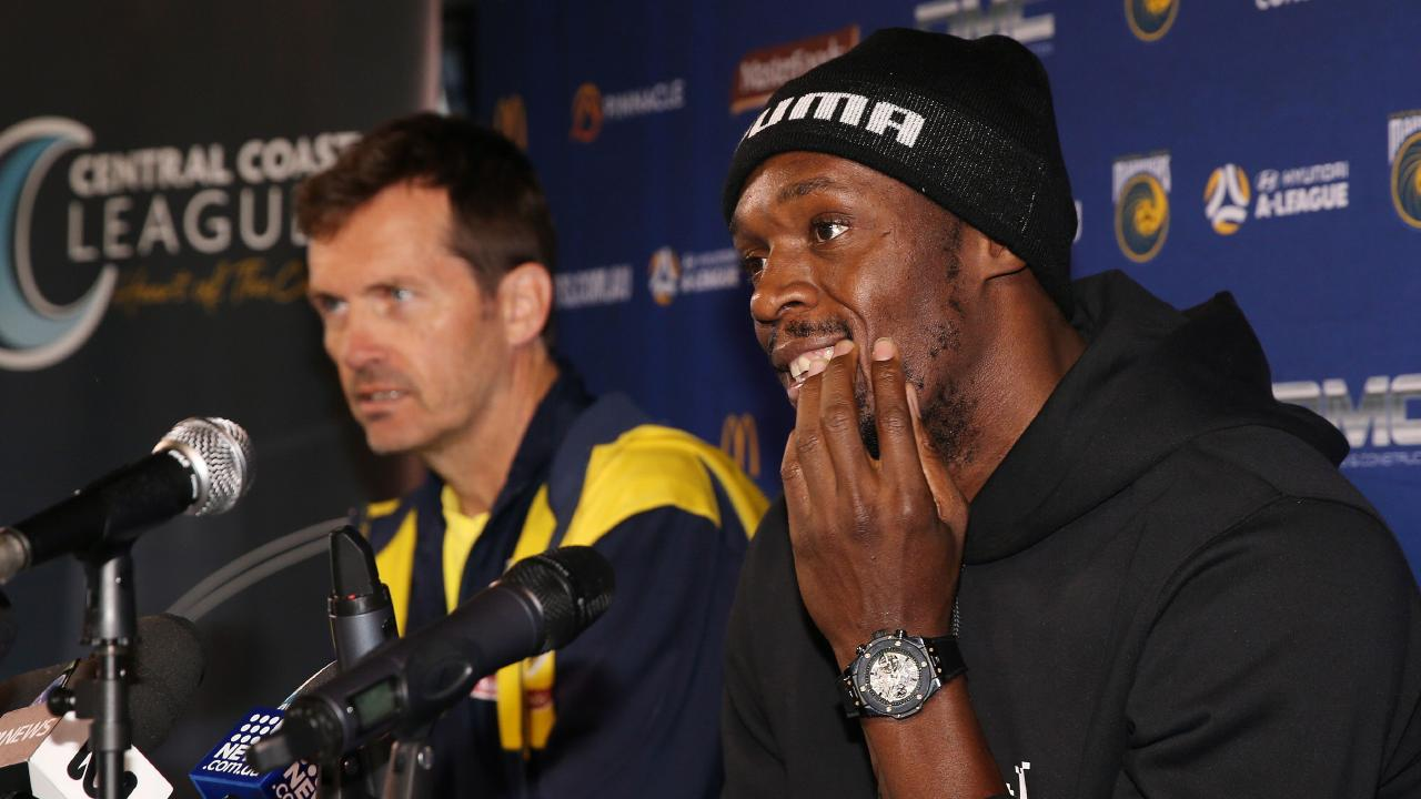 Thirty-one-year-old eight-time Olympic champion Usain Bolt (R), accompanied by A-League football club Central Coast Mariners coach Mike Mulvey, speaks at a press conference after training with the Mariners for the first time in Gosford on August 21, 2018. (Photo by PETER LORIMER / AFP) / --IMAGE RESTRICTED TO EDITORIAL USE - STRICTLY NO COMMERCIAL USE--