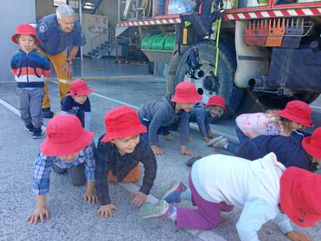 Children learn what to do in case of fire from local firefighters.