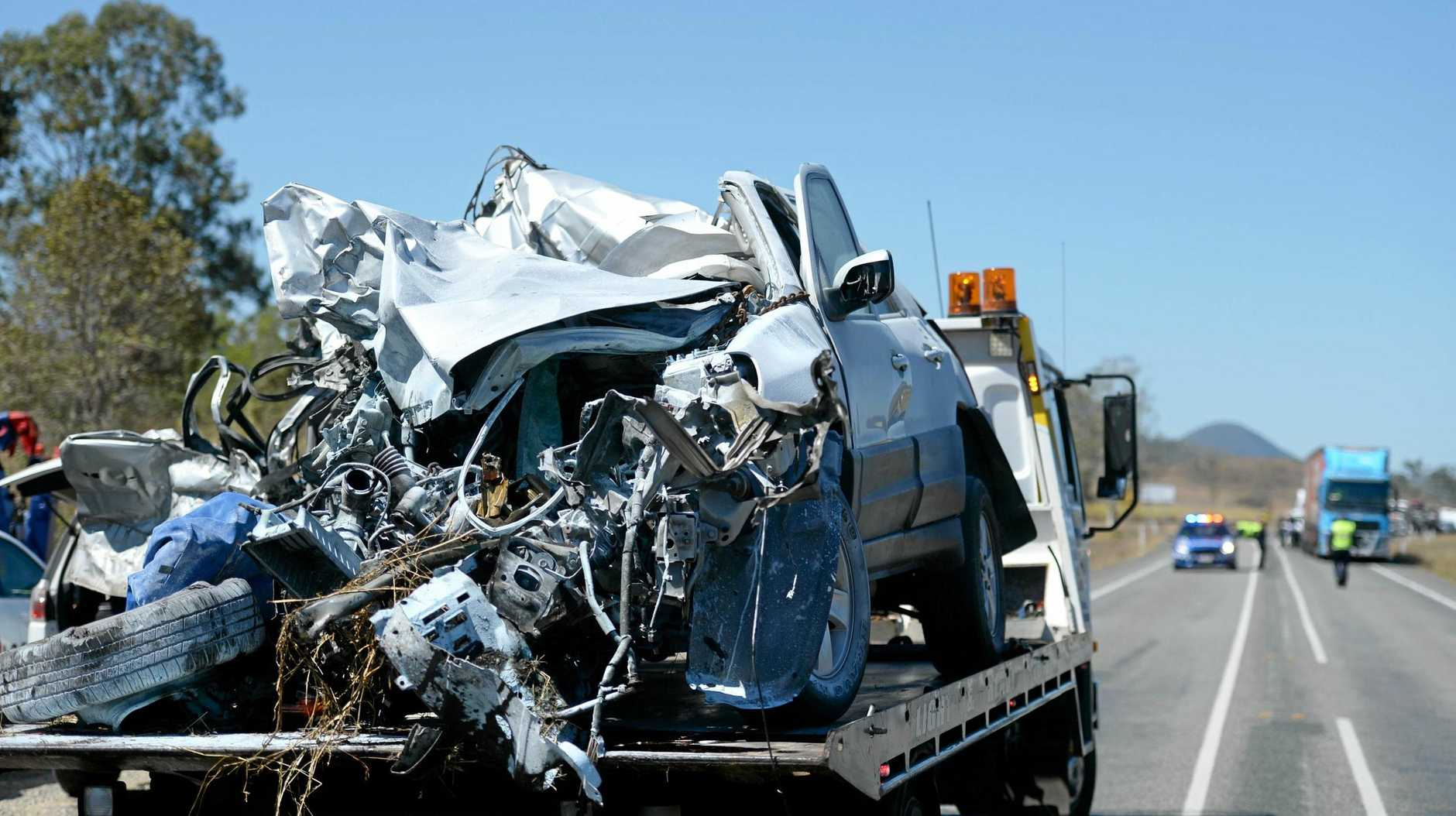 The wreckage of the vehicle is removed from the crash scene on the Bruce Highway near Bloomsbury.