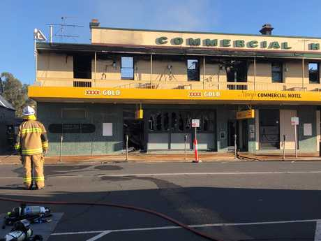 FIRE DAMAGE: Fire fighters assess the damage caused by a huge blaze at Dalby's Commercial Hotel.