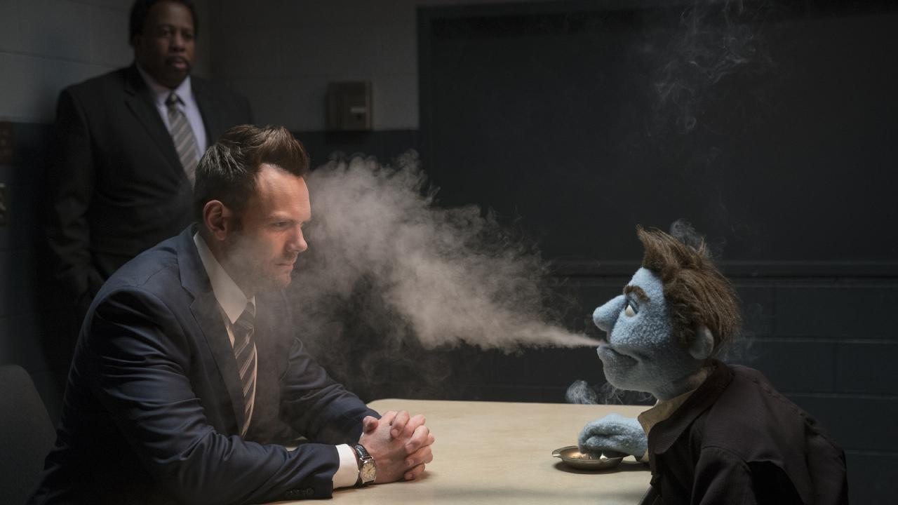 Agent Campbell (Joel McHale) gets a face full of smoke from Phil Philips (voiced by Bill Barretta) in The Happytime Murders.
