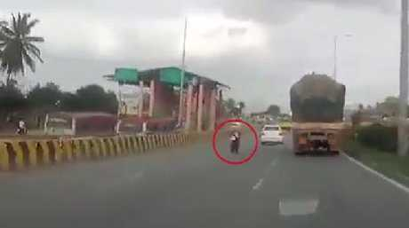 The riderless motorbike went behind a big truck before slamming into a road divider.