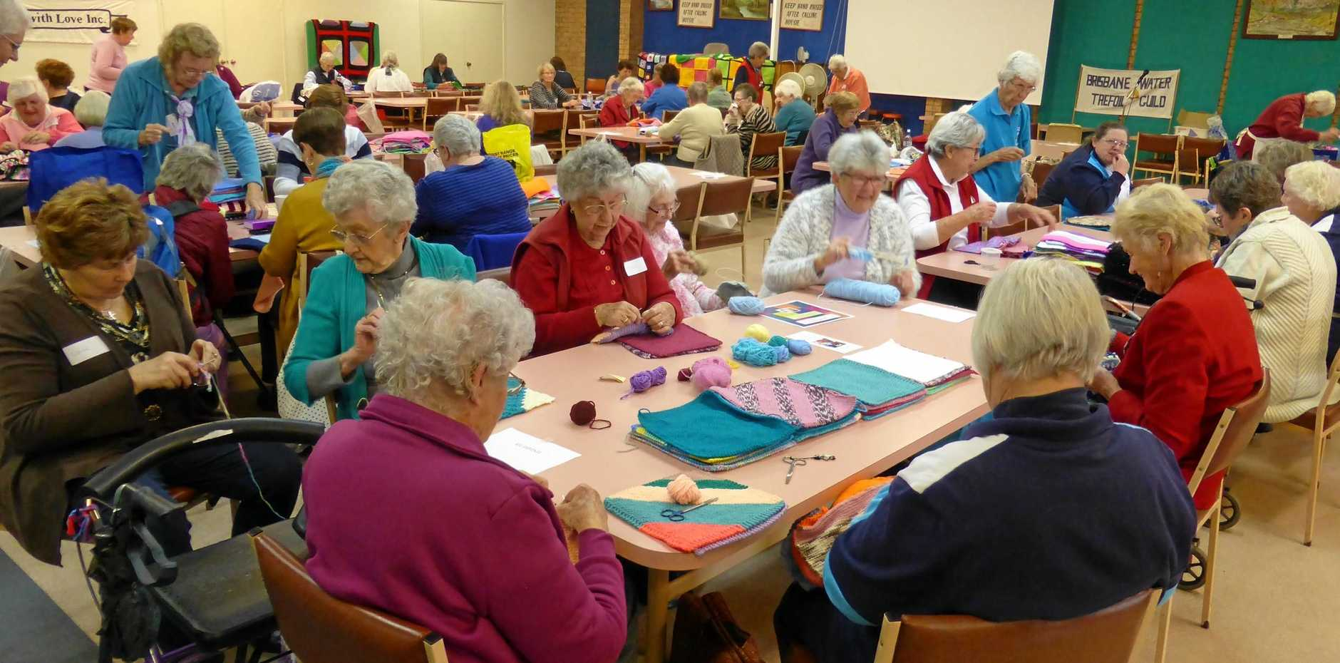ALL SEWN UP: Participants at a previous Wrap with Love knitting day, sewing together donated squares to make blankets to be donated to those in need.