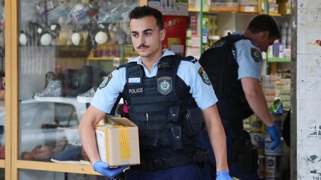 Police raid a store in Bankstown where thousands of tins of baby formula were found. Picture: David Swift.
