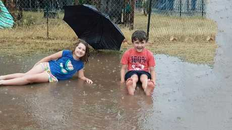 Giselle and Jett Challenger in their backyard at St George. The region received about 50mm of rain in the 24 hours to 9am Saturday.
