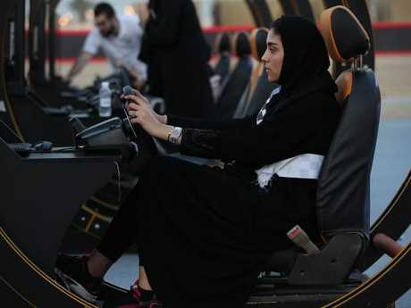 A young woman in Jeddah tries out a driving simulator at an outdoor educational driving event for women on June 23, 2018. Picture: Sean Gallup/Getty Images