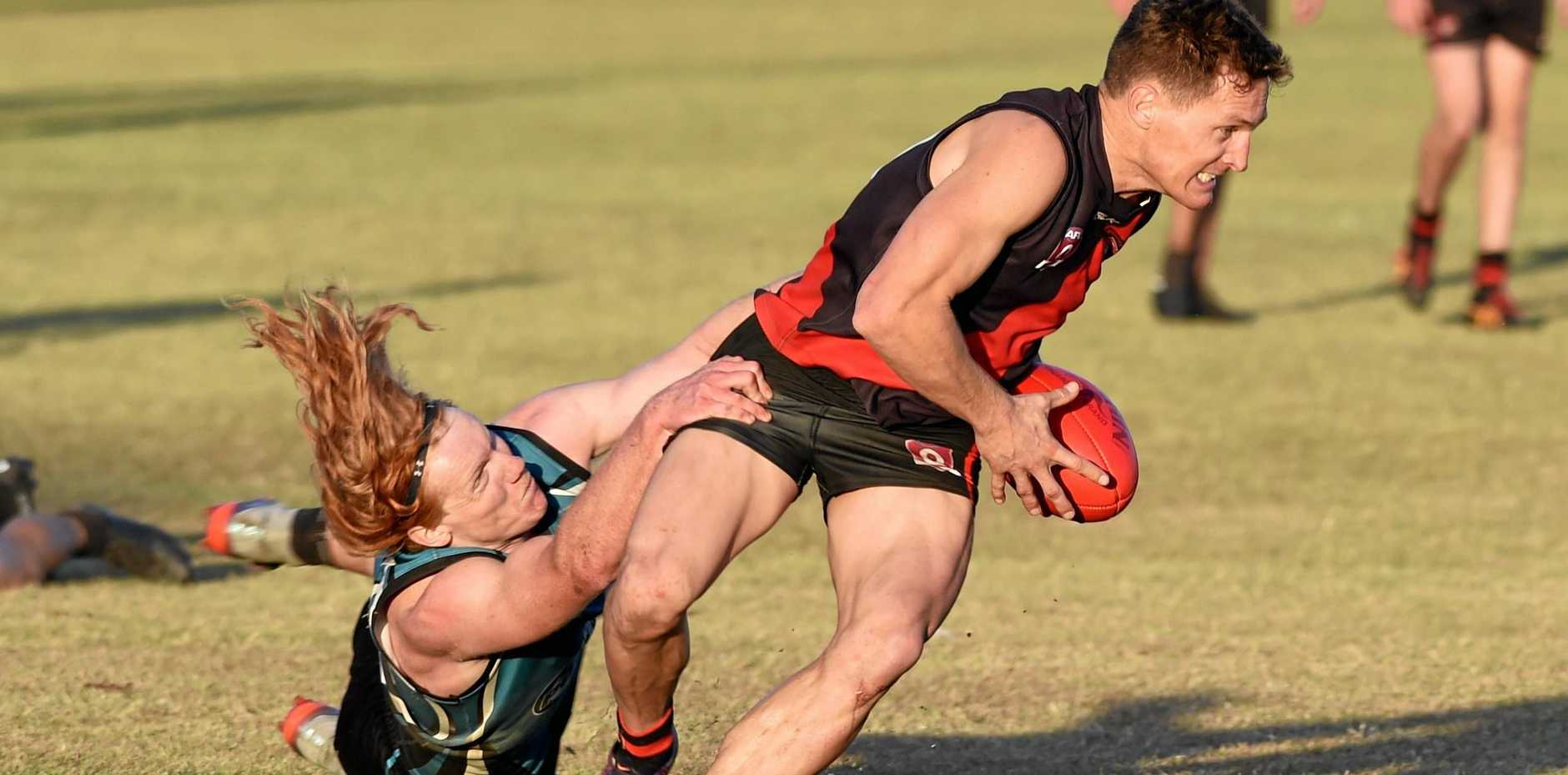 JOB DONE: Bay Power's Marcus Dyson tries to hold on to Hervey Bay Bomber Travis Mills in the AFL Wide Bay preliminary final. Mills kicked two goals in the 58-point victory.
