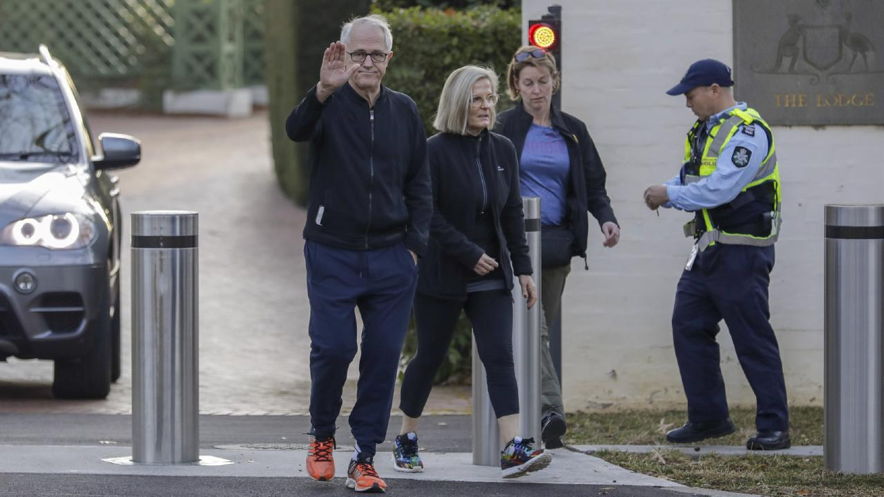 Malcolm Turnbull leaves The Lodge in Canberra with wife Lucy on his morning walk on Sunday and waves to the waiting media. Picture: Sean Davey