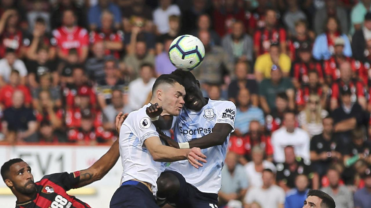 Everton's Michael Keane centre left and teammate Idrissa Gueye clash heads as they vie for the ball