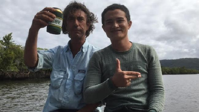 Justin Ward sharing a beer and a cigarette with an asylum seeker, believed to be from Vietnam, rescued from mangroves in the Daintree River