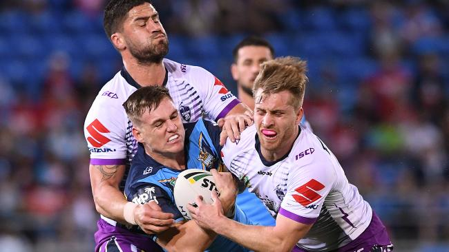 AJ Brimson of the Titans is tackled by Jesse Bromwich (left) and Cameron Munster of the Storm during the Round 24 NRL match between the Gold Coast Titans and the Melbourne Storm at Cbus Super Stadium. Photo: AAP