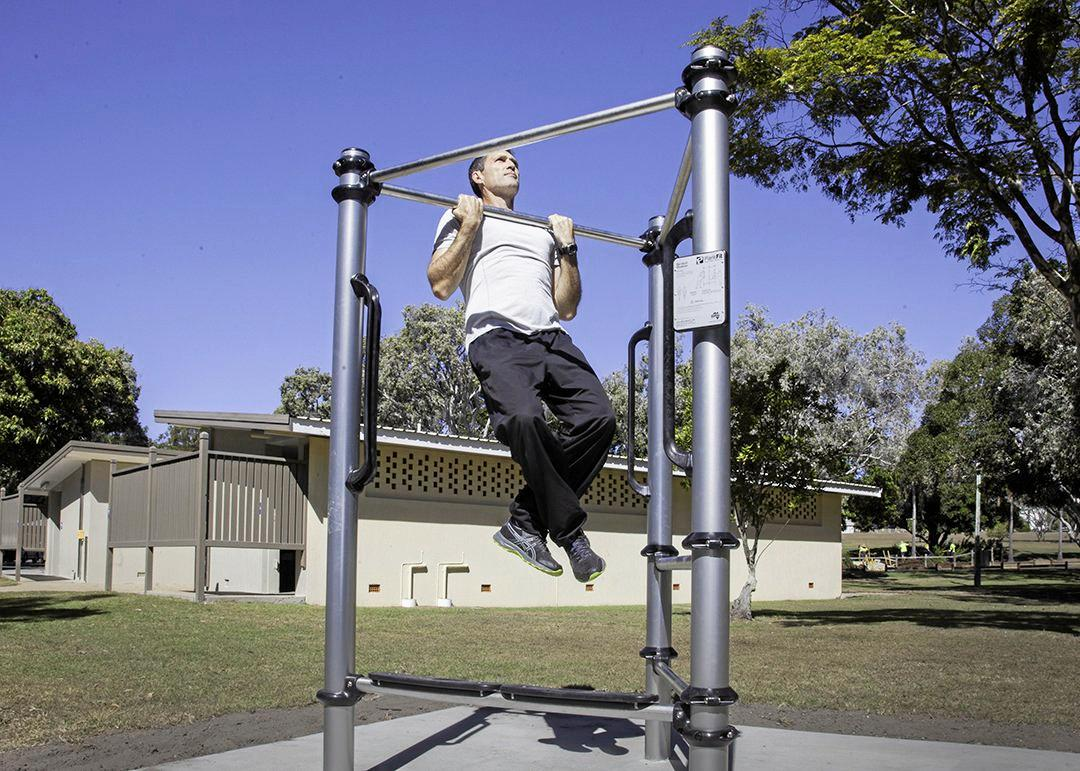 Division 10 Councillor Zane O'Keefe demonstrates how the new exercise equipment at Lower Dayman Park, Urangan, can be used.