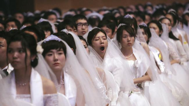 A bride yawns during a mass wedding ceremony in South Korea. Picture: AP Photo/Ahn Young-joon