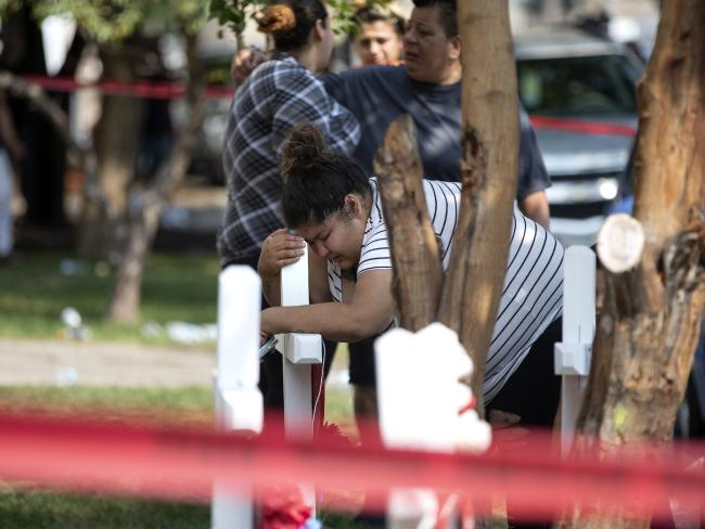 Amber Ayala, who lost siblings in a fatal Chicago fire, hugs a wooden cross outside the apartment building. Picture: Erin Hooley/Chicago Tribune