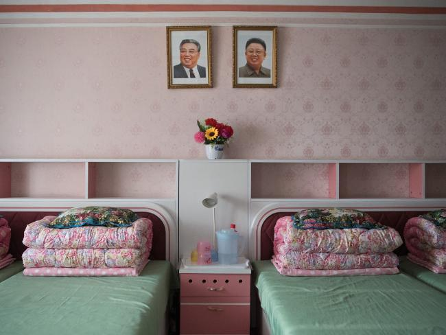 Pictures of Kim Il-sung and Kim Jong-il hang over beds in accommodation quarters at the Kim Jong Suk silk factory. Picture: Carl Court/Getty Images