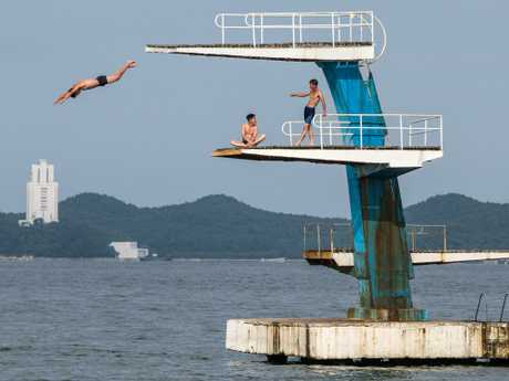 A man dives into the sea from a platform in Wonsan, North Korea. Picture: Carl Court/Getty Images