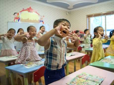 Children gesture and shout at the instruction of a teacher at Gyongsang Kindergarten. Picture: Carl Court/Getty Images