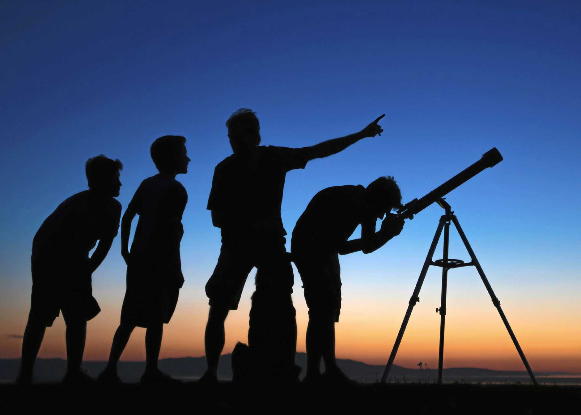 TAKE A LOOK: Dad kids looking through a refractor telescope.