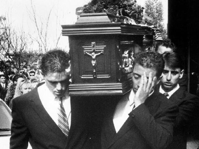 Fittler (left) and Alexander's brother Greg (hand across face) help carry the coffin at Ben Alexander's funeral.
