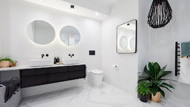 One of Kerrie and Spence's bathrooms, complete with a stone-top double-vanity, circular shaving cabinets, a slim line toilet and large bath. Source: The Block