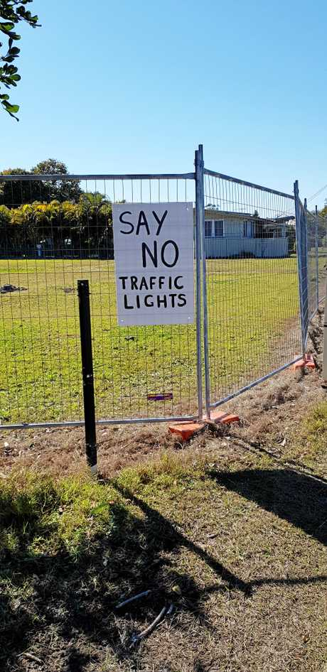 PROTEST: Placards appear on the fence surrounding the site of an approved service station on the corner of Treelands Dr and Yamba Rd.