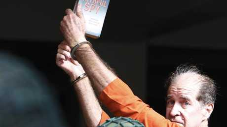 James Ricketson holds a book with the title of