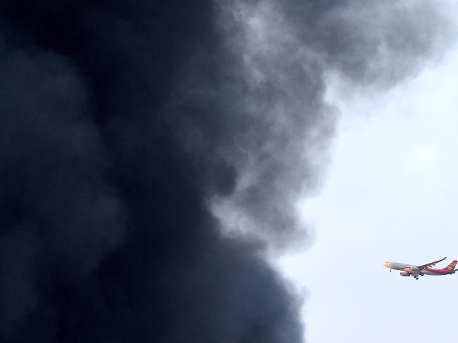 A commercial plane flies past the fire on Thursday. Picture: Nicole Garmston