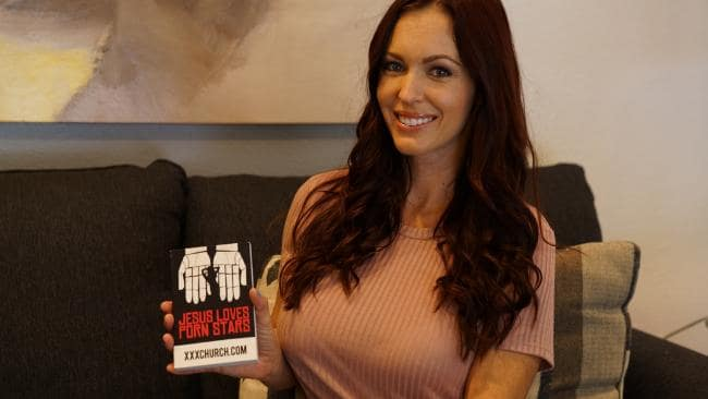Evangelical preacher Brittni De La Mora, formerly one of the world's most successful porn stars, poses with a flyer for the XXX Church, an organisation that supports people struggling with porn addiction. Picture: Barcroft Media/Getty Images
