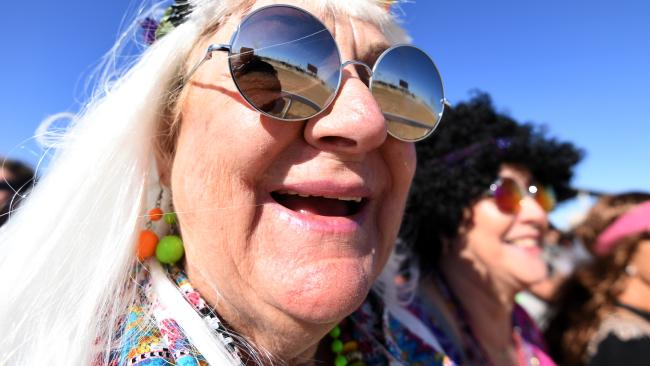 Racegoers in hippie costumes watch the Birdsville races. Picture: AAP Image/Dan Peled.