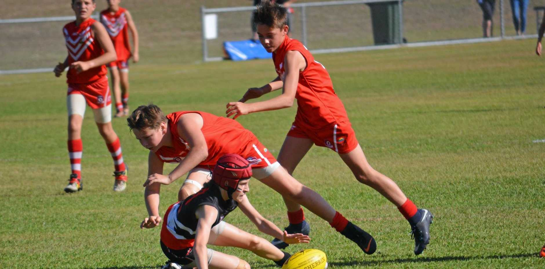 DESPERATE: Brooke Sheridan fights hard for the ball in Saturday's thrilling under-13 final.
