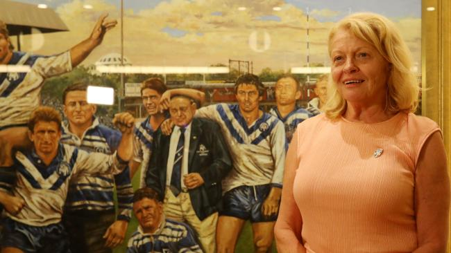 Lynne Anderson, the daughter of Canterbury patriarch Peter Moore poses next to a painting of her father after the Canterbury board elections, where it was announced she is set to take the place of Ray Dib as Chairman of the Bulldogs.