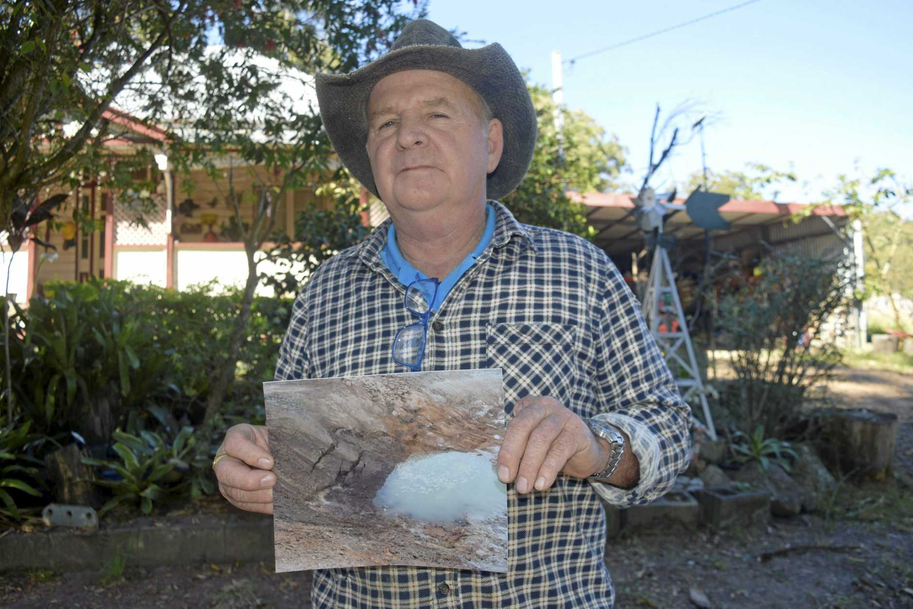 Phil Marcus with a photograph of the groundwater seeping through in one of the sediment dam.