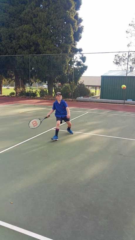 Bryn Cunningham returns a shot during Toowoomba Orange Ball tennis.