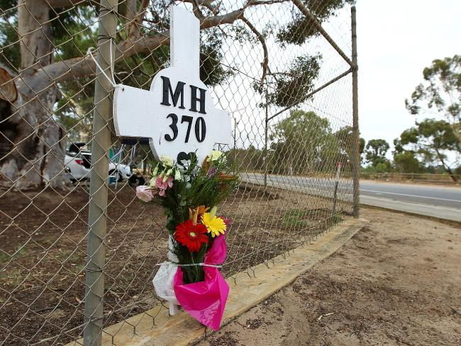 Flowers and a memorial for the missing passengers of flight MH370 are attached to the perimeter fence of RAAF Pearce Airbase near Perth. Picture: Getty Images