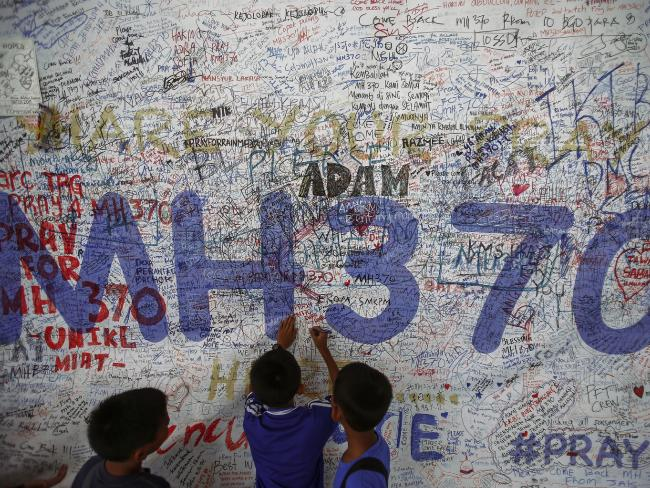 Children write messages on a mural after the plane went missing. Picture: Supplied