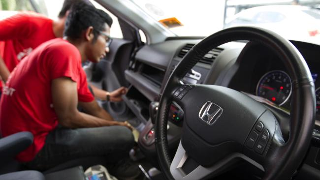 A Honda technician replaces a faulty Takata airbag. A loophole in the recall process means that private sellers in Australia of affected cars don't have to tell buyers about the recall.