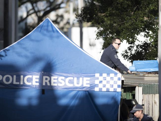 Surry Hills Terror raid property. Police officers still collecting evidence, taking in extra tarp to cover garage area of property. Picture's darren leigh roberts