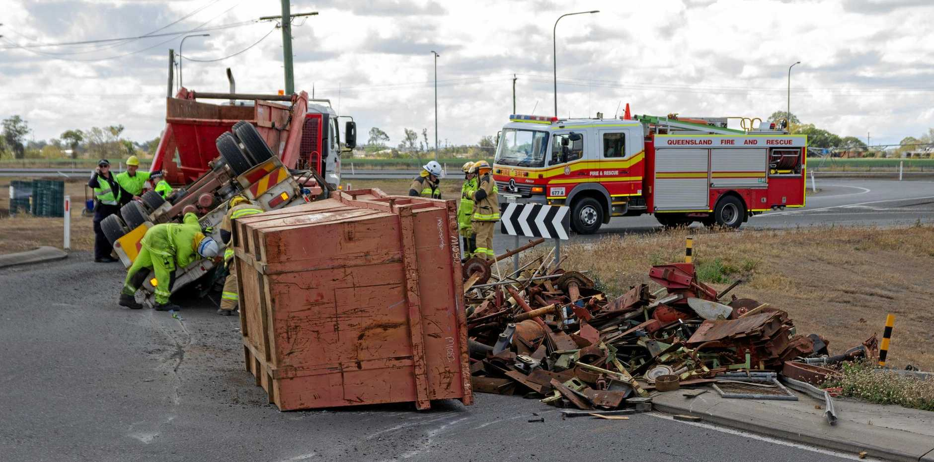 A truck's trailer has rolled on the roundabout connecting Eastern Drive with the westbound lanes of the Warrego Highway, spreading debris across the road.